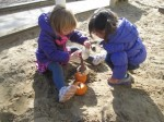 Scooping sand together in the sandbox